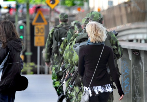 fashion street soldiers patrol Stockholm woman machine guns